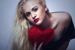 Belle femme blonde avec le coeur rouge. Fille de beauté. Montrez le symbole d'amour. Jour de valentines Photo libre de droits