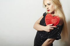 Belle femme blonde avec le coeur rouge. Fille de beauté. Montrez le symbole d'amour. Le Day.Passion de Valentine Photo libre de droits
