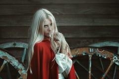 Belle femme blonde avec le manteau rouge Images stock