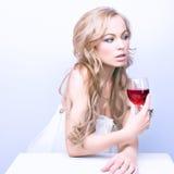 Belle femme blonde avec le vin rouge en verre photo stock