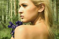 Belle femme blonde avec les fleurs bleues dans une forêt Image stock