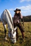 Belle femme blonde chez un cheval se tenant prêt de chapeau Images stock