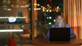 Belle femme blonde d'affaires travaillant des heures supplémentaires la nuit dans le bureau exécutif Les lumières de ville sont v banque de vidéos
