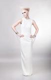 Belle femme blonde dans la longue robe blanche avec le hairstyl créatif images libres de droits