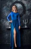 Belle femme blonde dans la robe bleue dans l'intérieur foncé image stock