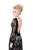 Belle femme blonde dans la robe de soirée noire élégante avec la coiffure d'updo Madame regardant au-dessus de son épaule sur le  photo libre de droits