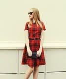 Belle femme blonde dans la robe rouge, lunettes de soleil avec l'embrayage de sac à main Photographie stock libre de droits