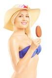 Belle femme blonde dans le bikini mangeant une crème glacée  Images stock