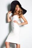 Belle femme blonde dans le chapeau noir et la robe de soirée élégante blanche posant sur le fond Regard de mode élégant Photo stock