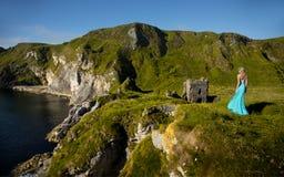 Belle femme blonde dans robe verte de turquoise la longue, au bord de mer à côté d'une ruine médiévale en Irlande photos stock