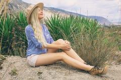 Belle femme blonde dans un chapeau Se repose à l'air frais sur la prairie Mystérieusement souriant et regardant le ciel photo libre de droits