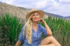Belle femme blonde dans un chapeau Se repose dehors sur la prairie Mystérieusement souriant photo libre de droits