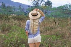 Belle femme blonde dans un chapeau Se repose dehors sur la prairie Mystérieusement souriant image stock