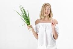 Belle femme blonde dans un chemisier blanc mangeant l'oignon amer vert sur le fond blanc Santé et vitamines Images stock