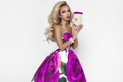Belle femme blonde dans une robe égalisante élégante avec les roses rouges, tenant le cadeau de Valentine, un flowerbox avec des  photographie stock