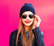 Belle femme blonde de sourire heureuse de portrait dans des lunettes de soleil noires, chapeau sur le mur rose coloré photographie stock