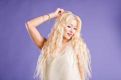 Belle femme blonde de sourire sur le fond violet image stock