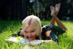 Belle femme blonde recherchant de la lecture photos libres de droits