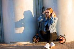 Belle femme blonde s'asseyant sur un scooter près du mur image stock