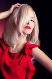 Belle femme blonde saisissante élégante sexy avec les lèvres rouges de maquillage lumineux dans une robe rouge dans le studio sur Photographie stock