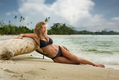 Belle femme blonde se trouvant près du tronc d'arbre sur la plage Photographie stock libre de droits