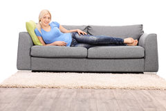 Belle femme blonde se trouvant sur un sofa gris moderne Photo stock