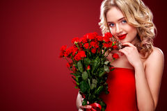 Belle femme blonde tenant le bouquet des roses rouges Jour international du ` s de femmes, célébration de huit mars Photo stock