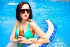 Belle femme bronzée dans le bikini et des lunettes de soleil se reposant dans le swimm Photo stock