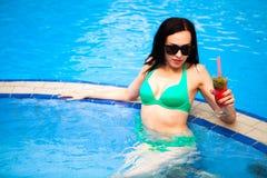 Belle femme bronzée dans le bikini et des lunettes de soleil se reposant dans le swimm Photographie stock libre de droits