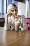 Belle femme buvant du chocolat chaud avec de la crème en café Image stock