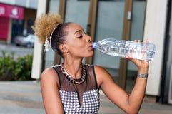 Belle femme buvant l'eau minérale Image stock