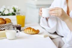 Belle femme buvant la boisson chaude à la table avec un croissant Photographie stock