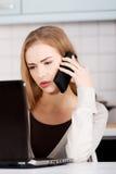 Belle femme caucasienne parlant par le téléphone et travaillant avec image libre de droits