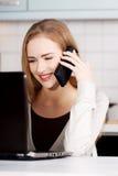 Belle femme caucasienne parlant par le téléphone et travaillant avec Photographie stock libre de droits
