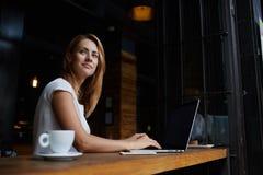 Belle femme caucasienne rêvant de quelque chose tout en se reposant avec le filet-livre portatif dans la barre moderne de café Photos stock