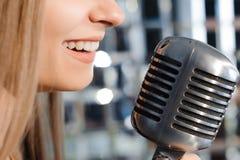 Belle femme chantant sur l'étape à côté du microphone photo stock