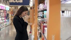 Belle femme choisissant des produits de soin de corps dans le supermarché, brune au centre commercial Photos libres de droits