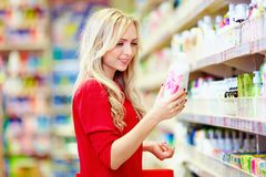 Belle femme choisissant le produit de soin personnel dans le supermarché Photo libre de droits