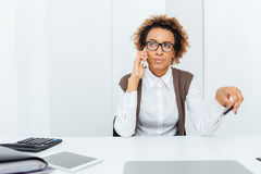 Belle femme comptable africaine s'asseyant et parlant au téléphone portable photos libres de droits