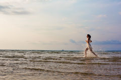 Belle femme courant sur la mer Images libres de droits