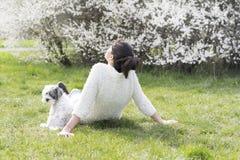 Belle femme détendant avec son chien de caniche blanc dans un jardin de ressort Photographie stock