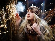 Belle femme détendant en paille en automne dans la chambre fumeuse Photo stock