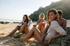 Belle femme détendant sur la plage avec ses amis Image stock