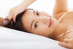 Belle femme détendant sur le lit Images stock