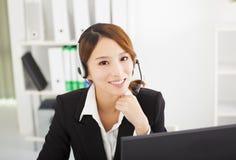 Belle femme d'affaires avec le casque dans le bureau Photo stock