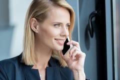 belle femme d'affaires blonde de sourire parlant par le smartphone et le regard Photographie stock
