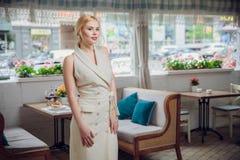Belle femme d'affaires blonde posant dans un restaurant photos stock