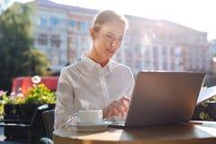 Belle femme d'affaires dactylographiant sur l'ordinateur portable en café Photographie stock libre de droits