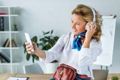 belle femme d'affaires dans des écouteurs prenant le selfie avec le smartphone photos stock