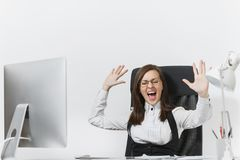Belle femme d'affaires dans le fonctionnement de costume et en verre à l'ordinateur avec des documents dans le bureau léger Images libres de droits